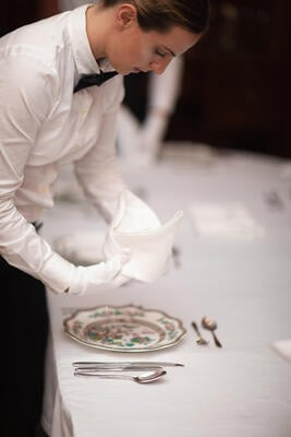 An academy student places a freshly folding napkin at a place setting